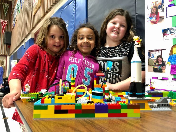 Three students proudly display a built Lego model