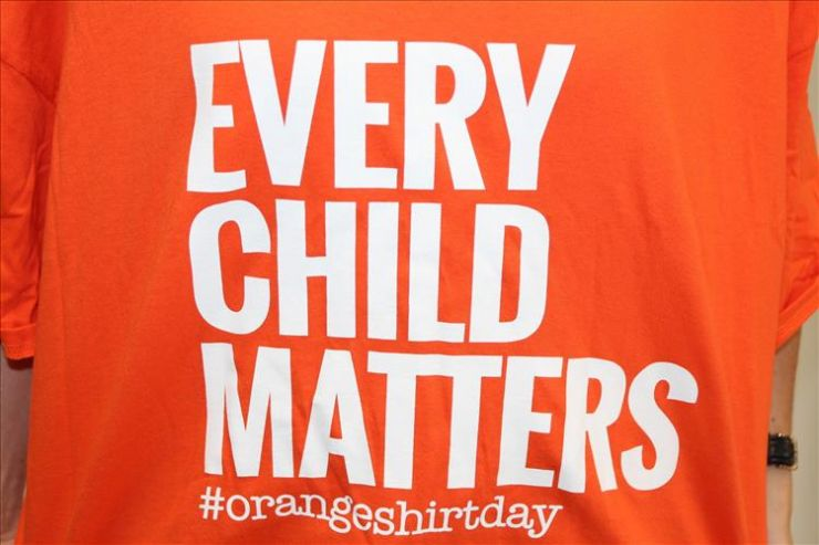 A close-up image of an orange t-shirt displaying the phrase Every Child Matters